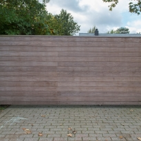 Vrijdragende schuifpoort met dubbelzijdige horizontale padouk houtbekleding - LM Hekwerk bvba
